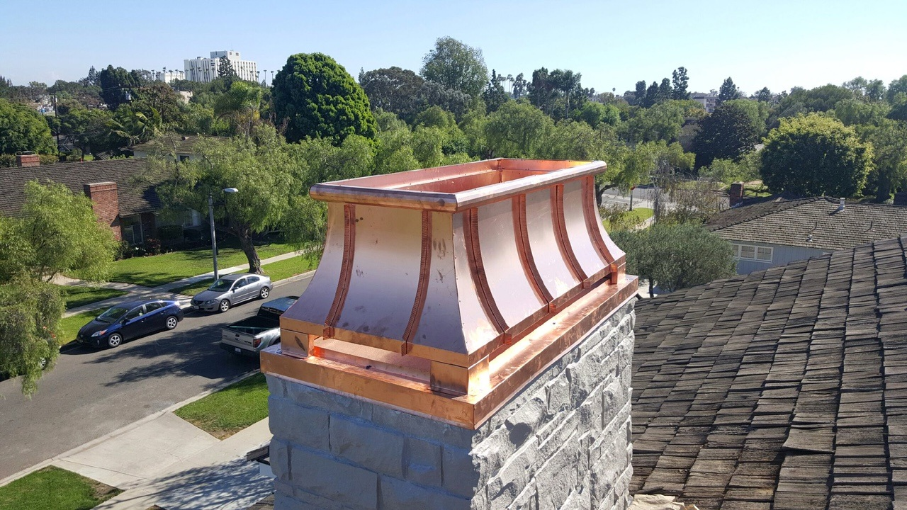Located at the top of a chimney - This is a covering that is used as housing, and it's sole purpose is to try and prevent various elements from entering the chimney. It is commonly used to keep out animals, snow, rain, sleet, branches, etc.
